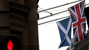 A Saltire and Union Jack flag hang side by side on a building in Edinburgh