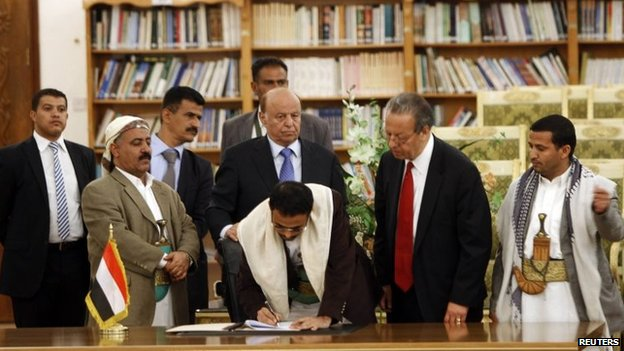 Mehdi al-Mashat, representative of Houthi leader Abdul Malik al-Houthi, signs an agreement, next to UN special envoy Jamal Benomar (second right) and Yemen's President AbdRabbuh Mansour Hadi (centre) in Sanaa (21 September 2014)