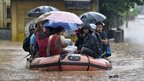Indian residents use an inflatable boat operated by the National Disaster Response Force (NDRF) to travel through floodwaters in Guwahati on September 22, 2014