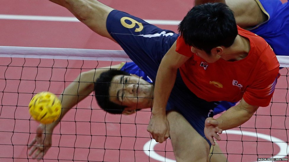 Thailand's Pornchai Kaokaew (left) strikes the ball over South Korea's Kim Young-man during their men's team sepaktakraw game