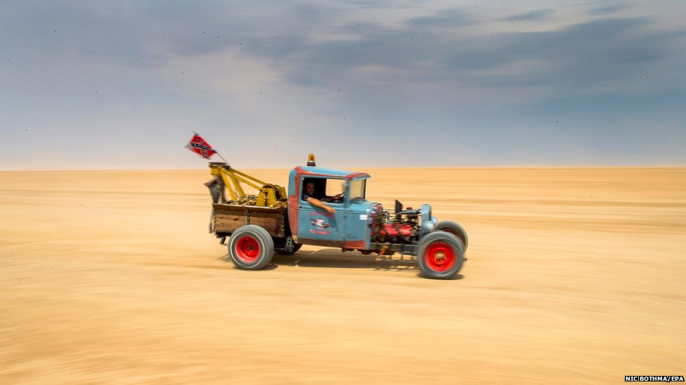 A modified 1928 Ford rat-rod drives across the Hakskeenpan