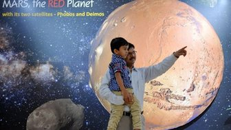 "A father and his son look at information about planet Mars on a poster put up at the Nehru Planetarium as a special preview on India""s Mars Orbiter Mission, in Bangalore on September 23, 2014."