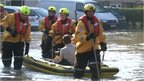Man in a boat lead by emergency service workers