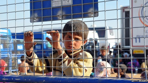 A young Syrian Kurdish refugee enters Turkey at the Yumurtalik crossing gate near Suruc on 23 September 2014 in Turkey.
