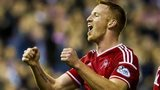Adam Rooney (left) celebrates his first and Aberdeen's second against livingston.