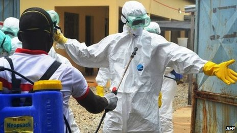 Guinea's Red Cross health workers wearing protective suits prepare to carry the body of a victim of Ebola at the NGO Medecins Sans Frontieres Ebola treatment centre near the hospital Donka in Conakry, 14 September 2014