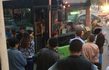 A crowd gathered around a bus