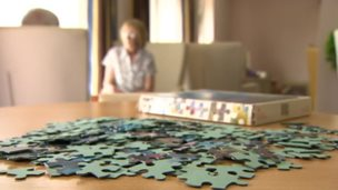 Jigsaw on table in foreground with older people out of focus in the background