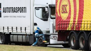An illegal migrant steps into a truck going to the UK on 10 September 2014 in the French port of Calais