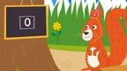 A squirrel next to a blackboard