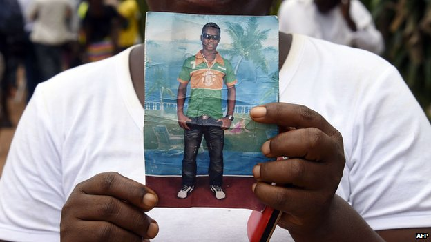 Liberian mother Mary holds a picture of her son Emaya, 20, who is suffering from Ebola and being treated at Island Hospital in Monrovia on September 26, 2014