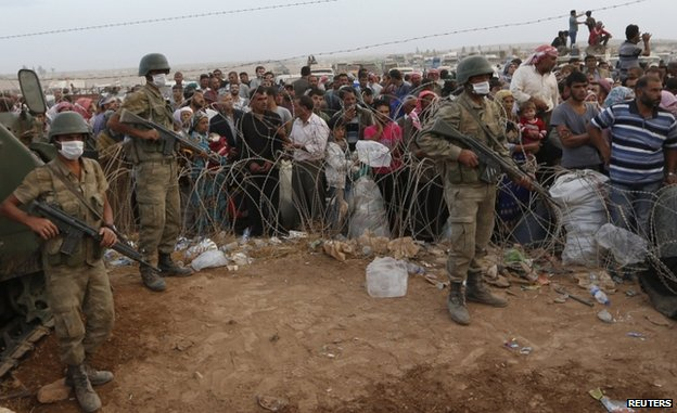Turkish troops stand guard as Syrian Kurdish refugees wait on the border at Suruc, 27 September