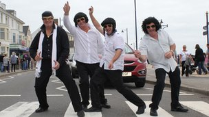 Four Elvis lookalikes on a road crossing