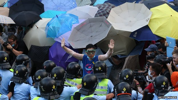 A pro-democracy demonstrator (C) gestures in front of a police line near the Hong Kong government headquarters on 28 September 2014.