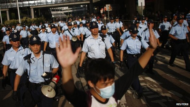A protester raises his arms as police officers try to disperse the crowd near the government headquarters in Hong Kong on 29 September 2014
