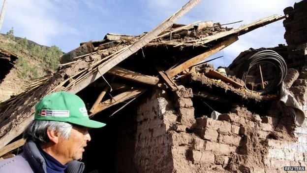 A man passes by the debris of a damaged house at a street in Paruro after the quake hit on 28 September, 2014.