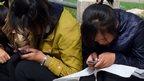 North Korean girls use mobile phones in a Pyongyang park