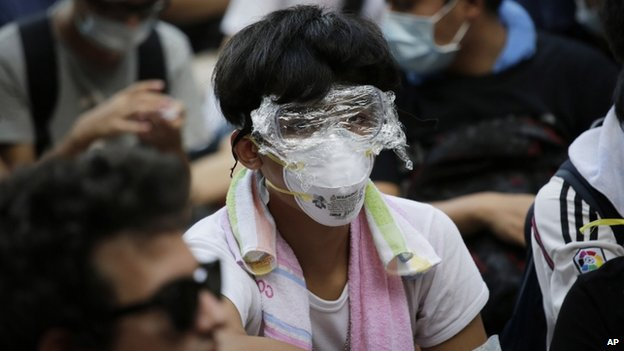 A protester with his face covered with plastic wrap to protect himself from tear on 29 September 2014