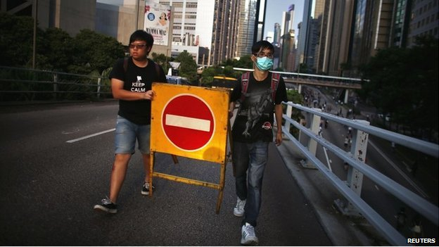 Protesters move a traffic sign as they try to block a street near the government headquarters in Hong Kong - 29 September 2014