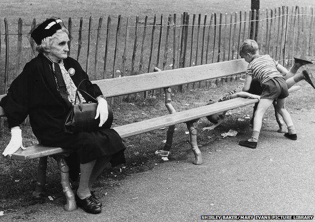 Elegant Elderly lady on a park bench with two unruly boys