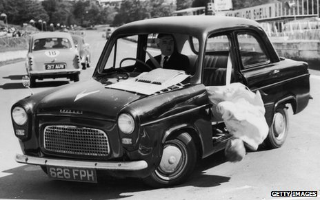 1964 Road safety campaign - a dummy falls out of a moving car because he is not wearing a seatbelt