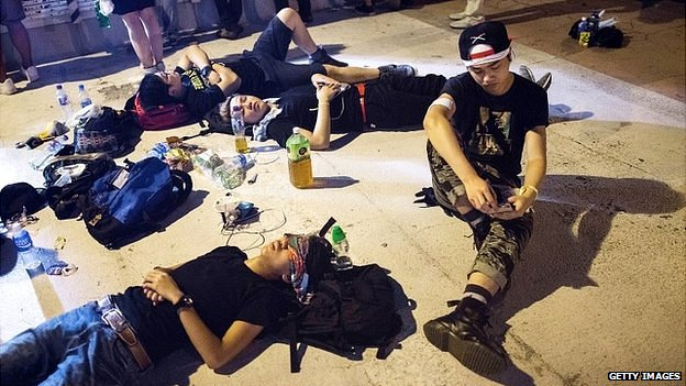 Protesters rest on the side of a street in the Central district in Hong Kong - 29 September 2014