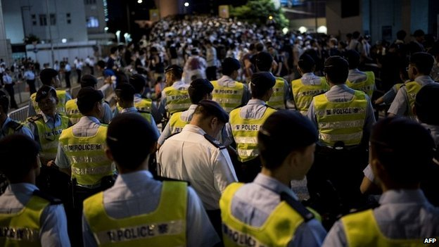 Police officers stand near a large group of pro-democracy protesters in the Wan Chai area of Hong Kong - 29 September 2014