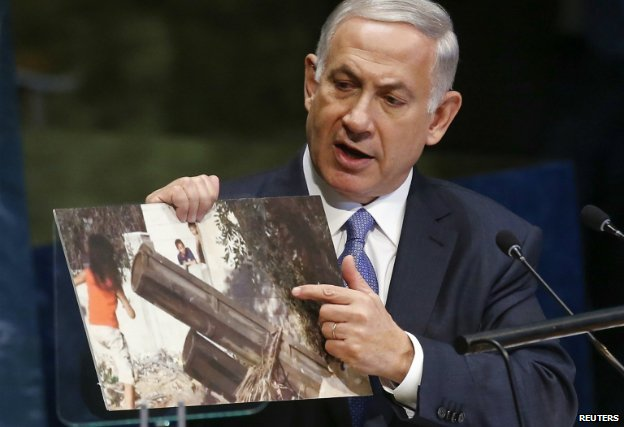 Prime Minister Benjamin Netanyahu shows an image of what he says was a Hamas rocket close to where children were playing in Gaza - 29 September 2014