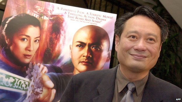 "Director Ang Lee poses in front of a poster of his Oscar-winning ""Crouching Tiger, Hidden Dragon"""