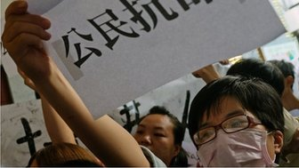 "A student protester displays a placard reading ""citizen disobey orders"" during a protest at the lobby of the Hong Kong office in Taipei on 29 September 2014"