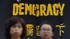 Pro-democracy protesters stand next to a banner in Hong Kong on 30 September 2014