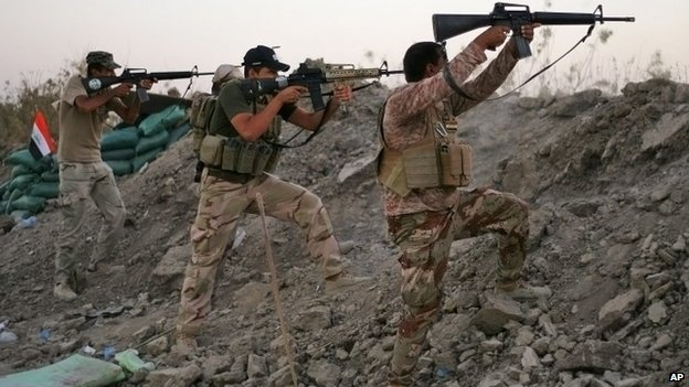 Iraqi Shia militiamen fire their weapons during clashes with militants from the Islamic State, in Jurf al-Sakhar, 50km south-west of Baghdad