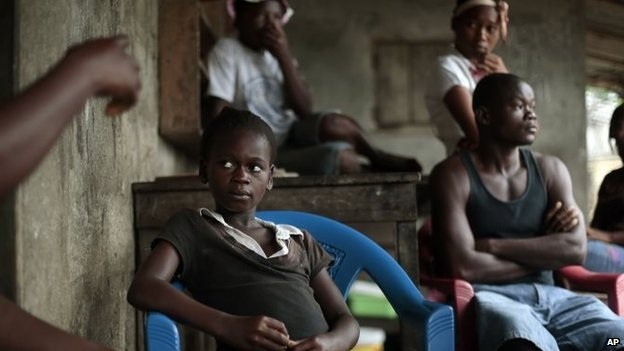 Kumba Fayiah, 11, sits with relatives in her St Paul Bridge home in Monrovia, Liberia. She lost both parents and her sister and has, recovered from the Ebola virus and is now living with her extended family