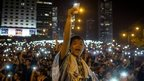 Protesters waving illuminated mobile phones
