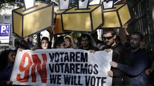 Pro-independence supporters hold a banner and cut-outs of ballot box during a protest in Madrid