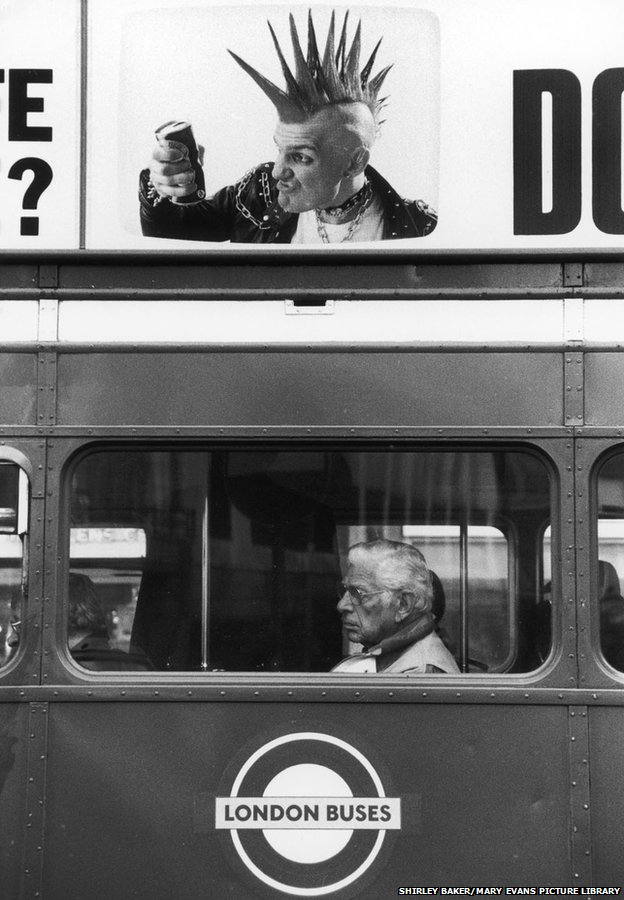 A terrific photograph showing the striking juxtaposition of a neat if stern elderly bus passenger framed in the window of the bus, set below an advert on the side of the vehicle depicting an angry punk