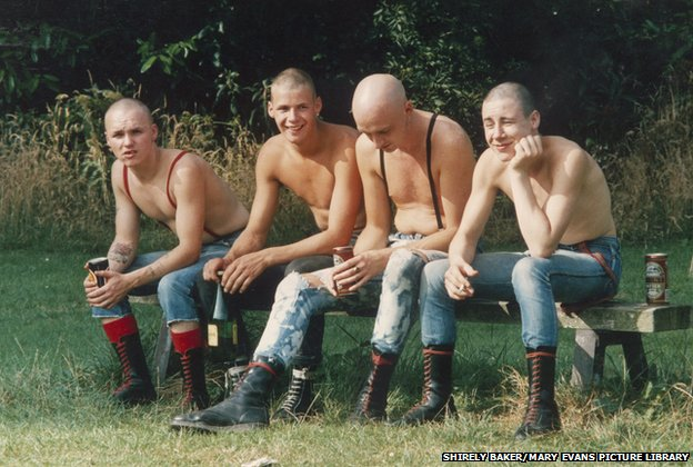 Four skinheads sit on a bench in a Wilmslow Park