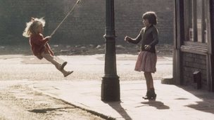 Two girls swing on a lamppost, Manchester 1965