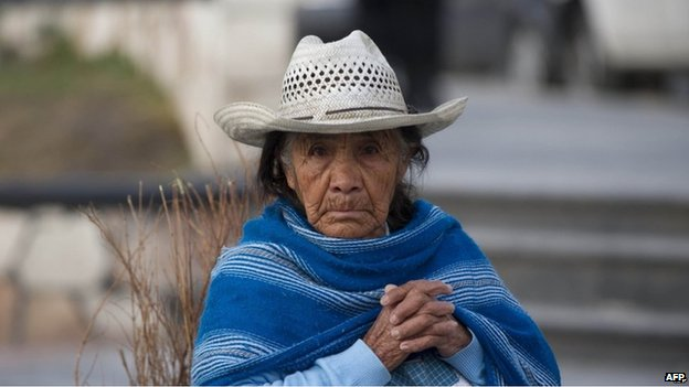 An older Mexican woman looks at the camera