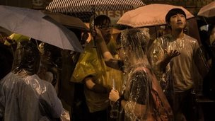 Protesters take shelter under umbrellas from heavy rain in Hong Kong on 30 September