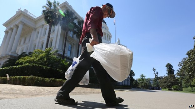 A man is seen carrying plastic bags in Sacramento, California, on 12 August 2014