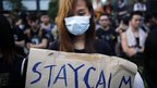"A student hold a sign which reads ""Stay Calm"" as protesters gather around the Golden Bauhinia Square before an official flag raising ceremony to commemorate the Chinese National Day in Hong Kong, on 1 October 2014"