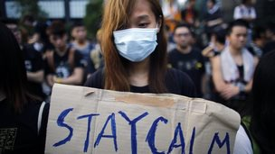 """A student hold a sign which reads """"Stay Calm"""" as protesters gather around the Golden Bauhinia Square before an official flag raising ceremony to commemorate the Chinese National Day in Hong Kong, on 1 October 2014"""