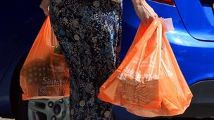 A shopper with Sainsbury's carrier bags