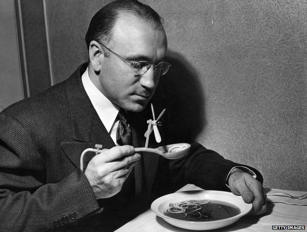 A man eating soup with a spoon with a fan on it