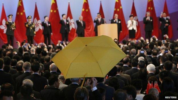 Paul Zimmerman, a district councillor, raises a yellow umbrella as Hong Kong Chief Executive Leung Chun-ying (5th R) addresses guests at a flag raising ceremony in Hong Kong on 1 October 2014