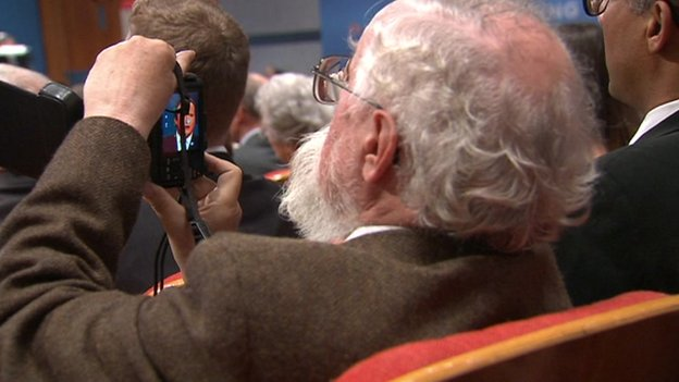 Audience member taking a picture of David Cameron