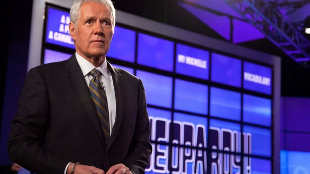 Host Alex Trebek stands on the set of the game show Jeopardy.