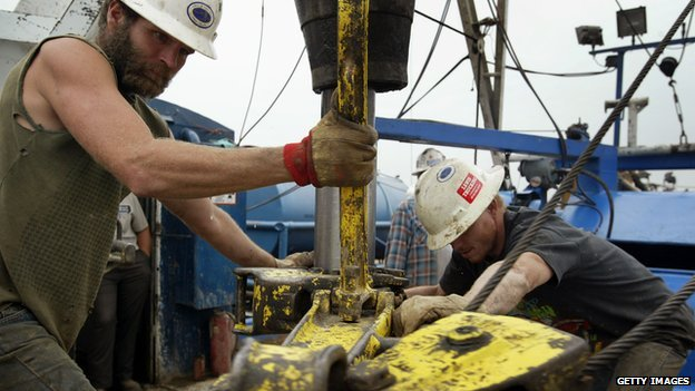Two men operate an oil rig in Illinois.