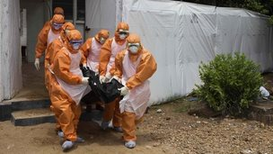 A burial team remove a body from an isolation holding centre in Port Loko, Sierra Leone - 27 September 2014